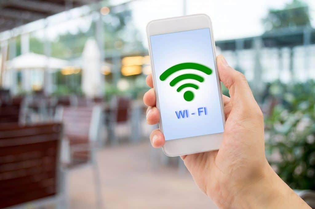 Hand holding cell phone with a wifi symbol